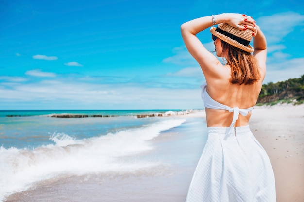 Young beautiful woman wearing straw hat and white swimsuit and skirt posing standing on beach near waves and looking away at the sea