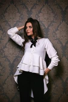 Молодая красивая женщина, носить стильную блузку и брюки