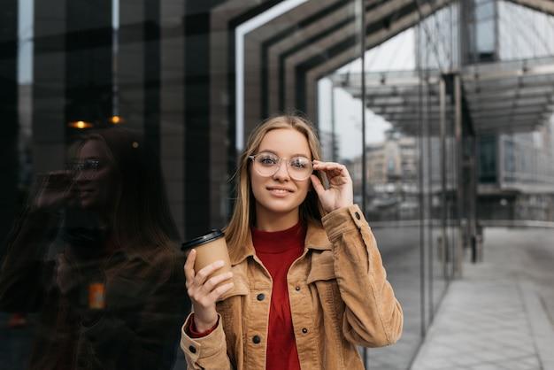 スタイリッシュな眼鏡、一杯のコーヒーを保持している、通りを歩いて若い美しい女性