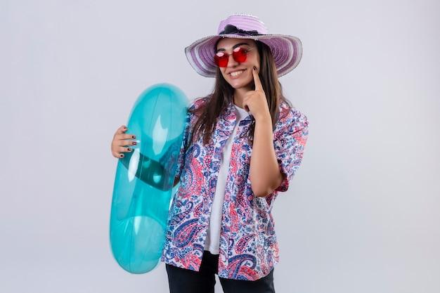 Молодая красивая женщина в летней шляпе и красных солнцезащитных очках держит надувное кольцо позитивно и счастливо улыбается, весело указывая пальцем на щеку, готовая к празднику