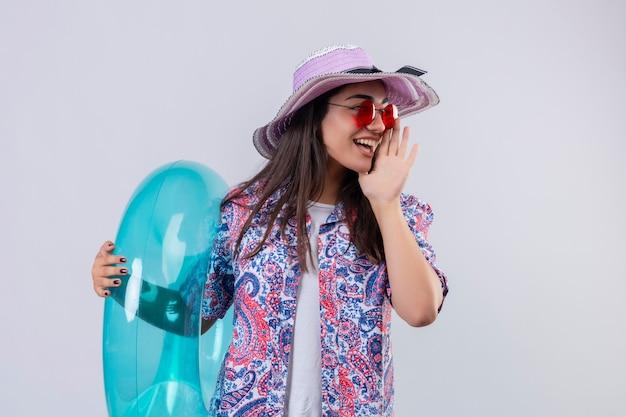 Молодая красивая женщина в летней шляпе и красных солнцезащитных очках держит надувное кольцо, кричит или зовет кого-то рукой возле рта, позитивно и счастливо смотрит в сторону, готовая к празднику концепции s