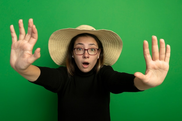 Giovane bella donna che indossa un cappello estivo in un dolcevita nero e occhiali guardando davanti tenendo le mani fuori facendo gesto di arresto spaventato in piedi sopra la parete verde