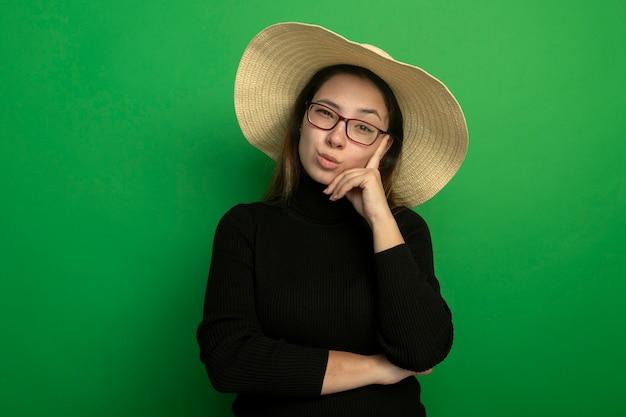 검은 터틀넥에 여름 모자를 쓰고 안경을 쓰고 회의적인 표정이 녹색 벽 위에 서있는 젊은 아름 다운 여자
