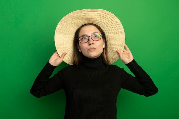 검은 터틀넥과 녹색 벽 위에 행복하고 긍정적 인 서를 찾는 안경에 여름 모자를 쓰고 젊은 아름다운 여자