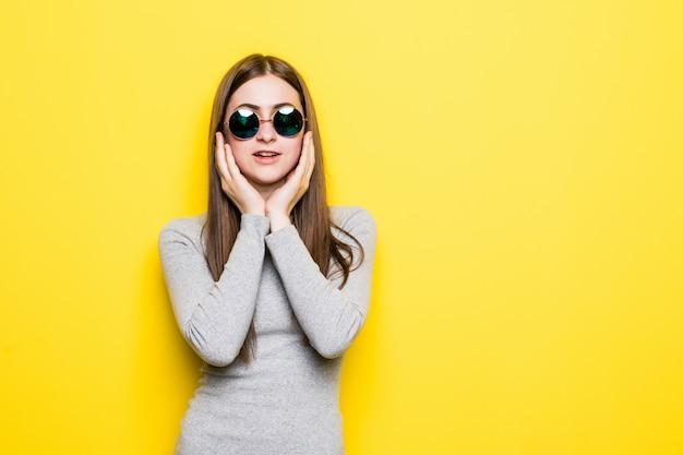 歯痛のため痛みを伴う表現で手で口に触れる黄色の孤立した壁に夏のスタイルとサングラスを着ている若い美しい女性
