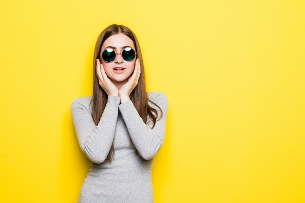 Young beautiful woman wearing summer style and sunglasses over yellow isolated wall touching mouth with hand with painful expression because of toothache