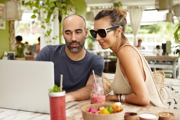 Giovane bella donna che indossa occhiali da sole e uomo barbuto seduto alla terrazza all'aperto e guardando qualcosa sul loro computer portatile generico durante la navigazione in internet, utilizzando la connessione wireless durante il pranzo