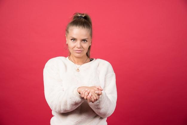 手のひらを一緒に赤い孤立した壁の上に立っているセーターを着ている若い美しい女性