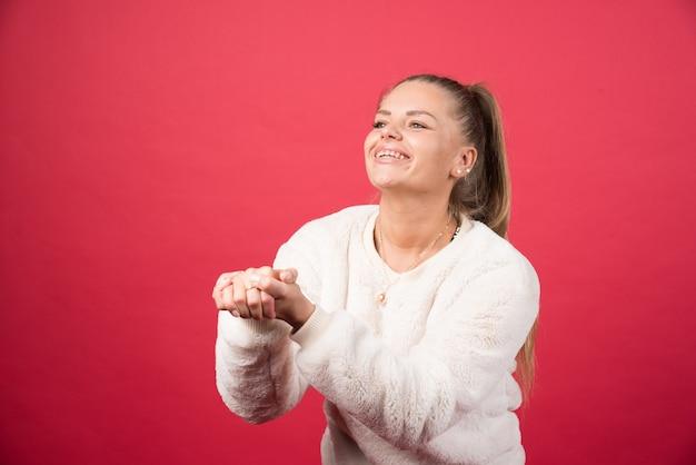 Молодая красивая женщина в свитере, стоящая над красной изолированной стеной с руками ладонями вместе