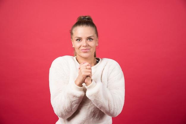 Giovane bella donna che indossa un maglione in piedi sopra il muro rosso isolato con le palme delle mani insieme