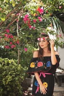 都市通りで伝統的なメキシコのドレスを着ている若い美しい女性