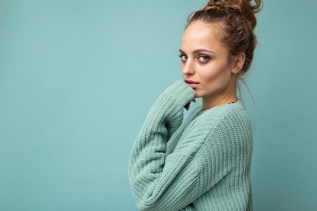 トレンディな青いセーターを着ている若い美しい女性