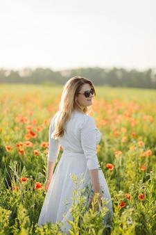 Молодая красивая женщина в белом платье позирует в маковом поле