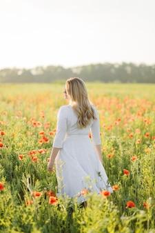 Giovane bella donna che indossa un abito bianco in posa in un campo di papaveri