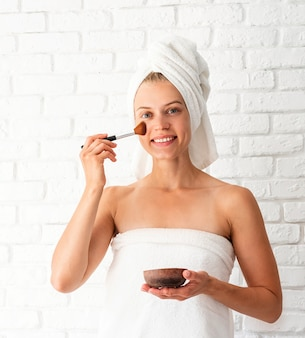 Young beautiful woman wearing white towels applying scrub on her face