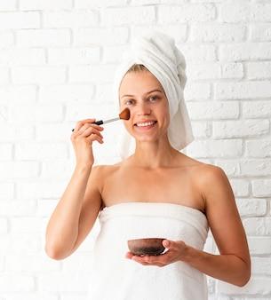 그녀의 얼굴에 스크럽을 적용하는 흰색 수건을 입고 젊은 아름다운 여자