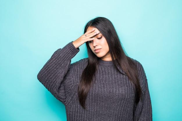 Молодая красивая женщина в зимнем свитере на изолированном синем страдает от головной боли, отчаявшейся и подчеркнутой из-за боли и мигрени. руки на голове.