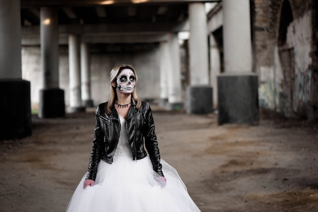 Young beautiful woman in wedding dress and skull make up