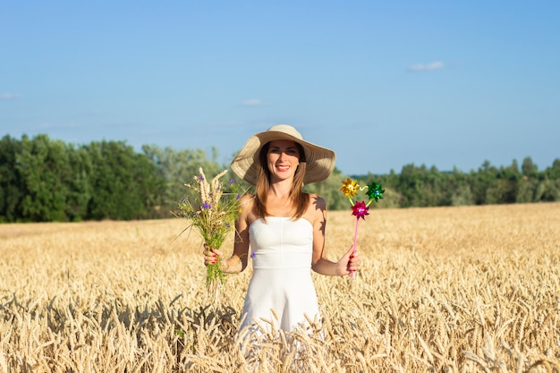 Young beautiful woman in a white dress and hat holds a bouquet with wildflowers and a toy visor on a milf's field.