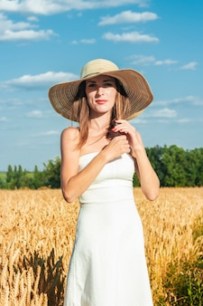 Young beautiful woman in a white dress and a hat on a milf's field.