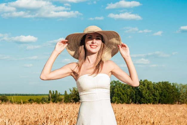Young beautiful woman in a white dress and a hat on a milf's field
