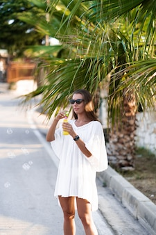 Young beautiful woman in white dress and sunglasses blowing soap bubbles on the road with palms. the concept of joy, ease and freedom during the vacation. the girl is enjoying the rest.