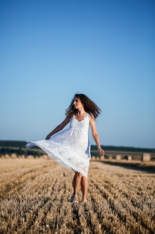A young beautiful woman in a white summer dress stands on a mown wheat field with huge sheaves of hay, enjoying nature. nature in the village. selective focus