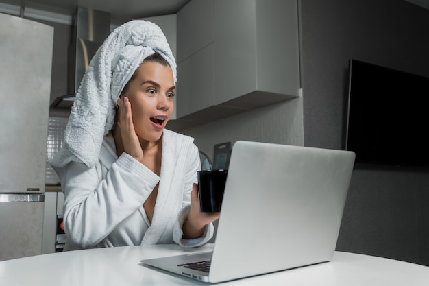 Young beautiful woman in white towel and robe drinking coffee and looking on laptop screen at the table