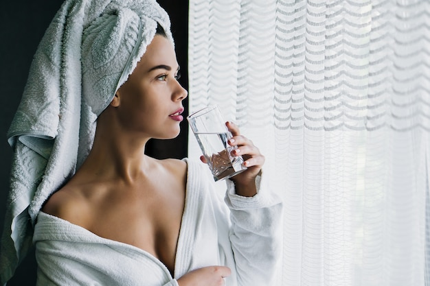 Young beautiful woman in white towel and robe drinking water near the window at home