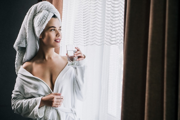 Young beautiful woman in white towel and robe holding a glass of water near the window at home