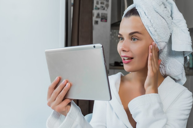 Young beautiful woman in white towel and robe holding a tablet