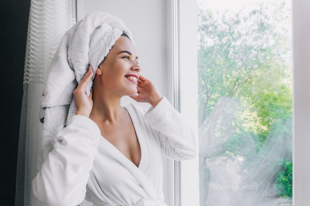 Young beautiful woman in white towel and robe locking through the window at home