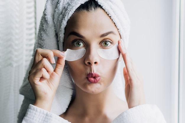 Young beautiful woman in white towel and robe taking off eye patch with funny face
