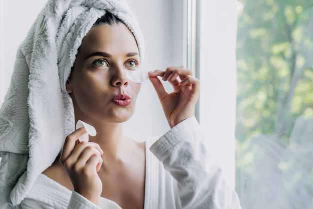 Young beautiful woman in white towel and robe taking off an eye patch with funny face