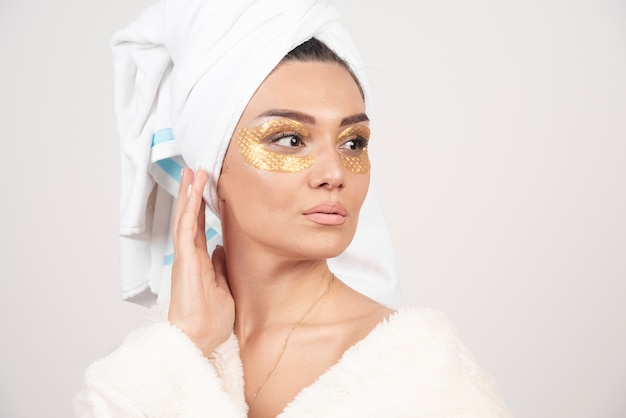Young beautiful woman in white towel and robe with eye patch