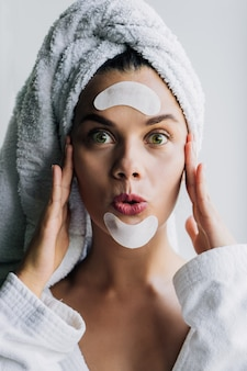 Young beautiful woman in white towel and robe with eye patches on her forehead and chin with funny face