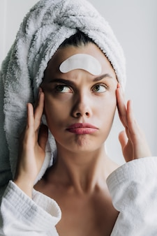 Young beautiful woman in white towel and robe with eye patches on her forehead posing with funny face