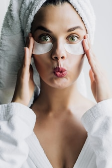 Young beautiful woman in white towel and robe with eye patches with funny face