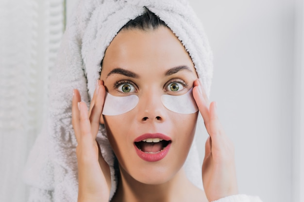Young beautiful woman in white towel and robe with eye patches with open mouth