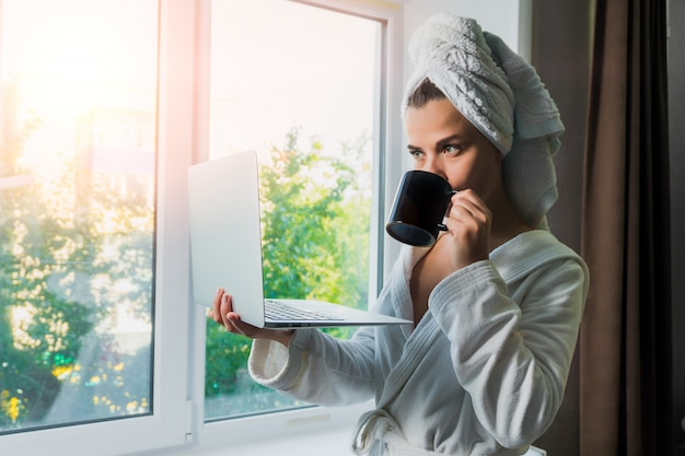 Young beautiful woman in white towel and robe with a laptop in her hand drinking coffee near the window