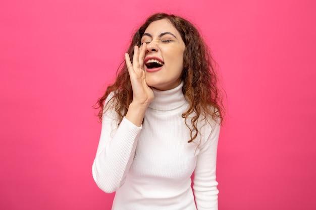 Giovane bella donna in dolcevita bianco che grida o chiama tenendo la mano sulla bocca in piedi sul muro rosa