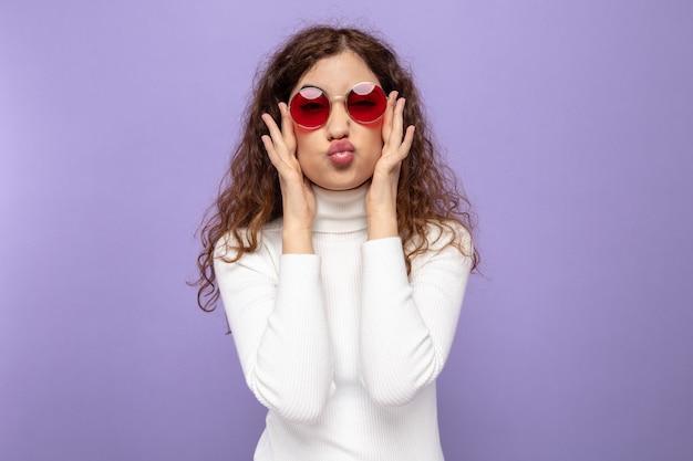 Giovane bella donna in dolcevita bianco che indossa occhiali rossi che sembra felice e positiva mantenendo le labbra come andare a baciare