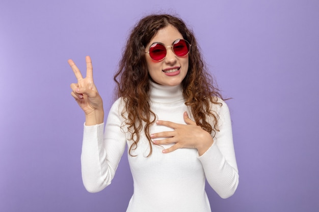 Young beautiful woman in white turtleneck wearing red glasses looking smiling cheerfully holding hand on her chest showing v-sign