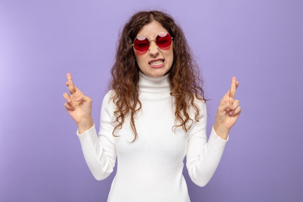 Young beautiful woman in white turtleneck wearing red glasses making desirable wish crossing fingers with hope expression standing on purple