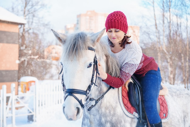 Young beautiful woman in winter with beautiful white horse