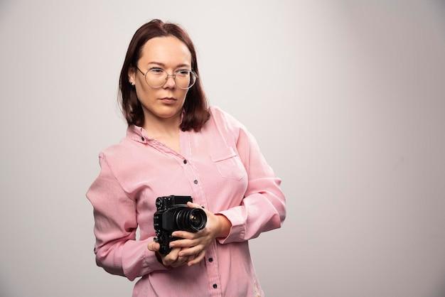 白のカメラを持つ若い美しい女性。高品質の写真