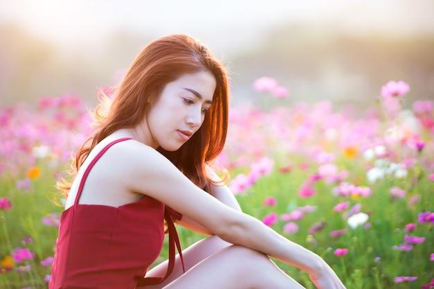 코스모스 꽃과 젊은 아름 다운 여자.