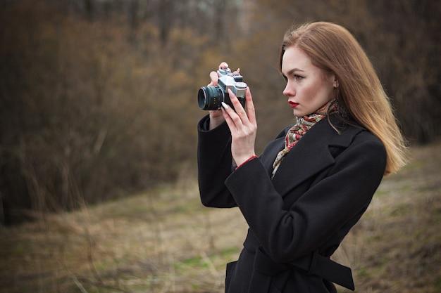 彼女の手に写真カメラを持つ若い美しい女性は、秋の自然の写真を撮ります。