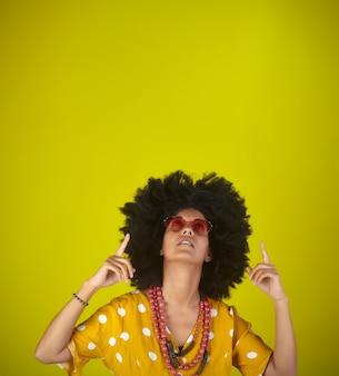 アフロの巻き毛のヘアスタイルとハート形の若い美しい女性を指して、指で方向を示す黄色の背景を指して見上げると眼鏡。 copyspace