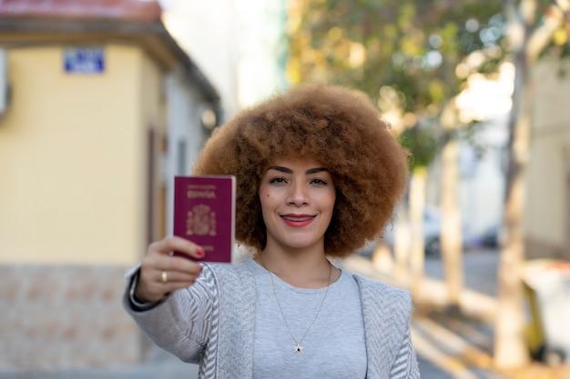 Молодая красивая женщина с афро-волосами, счастливая улыбающаяся на открытом воздухе в хороший день, показывает испанский паспорт